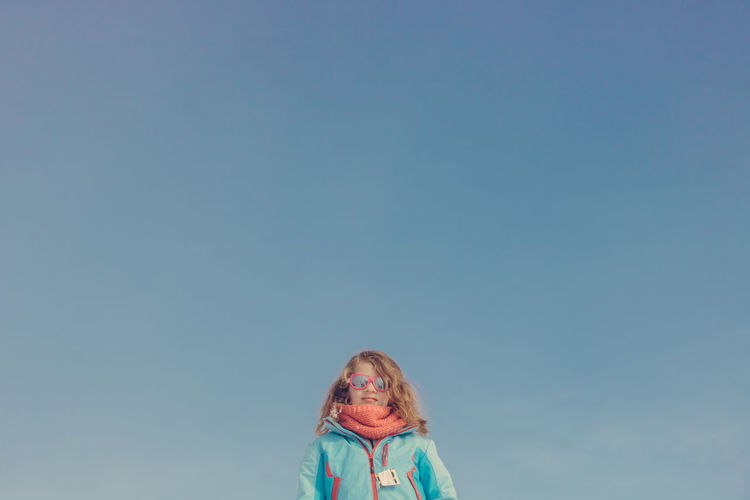 Portrait of girl against blue sky