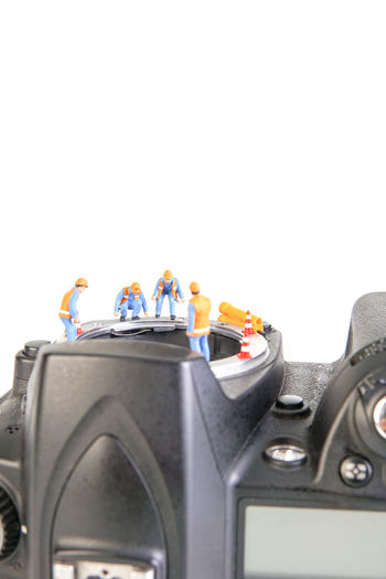 Miniature action figure workers - Close up of workers teamwork concept doing maintenance on digital single lens reflex (DSLR) body camera. Business Camera Camera Sensor Construction, DSLR Electronic RISK Service Teamwork Action Figure Broken, Close-up Compensation Components Damaged Dust, Maintenance Miniature Modified Progress Repair, Studio Shot Technician Warranty White Background