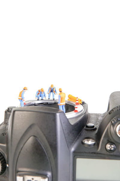 Miniature action figure workers - Close up of workers teamwork concept doing maintenance on digital single lens reflex (DSLR) body camera. Business Camera Camera Sensor Construction, DSLR Electronic RISK Service Teamwork Action Figure Broken, Close-up Compensation Components Damaged Dust, Maintenance Miniature Modified Progress Repair, Studio Shot Technician Warranty White Background