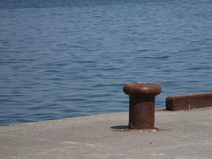 Close-up of wooden post on pier over sea