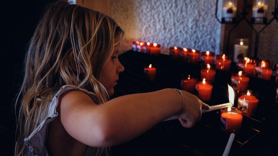 Close-up of girl holding illuminated candles