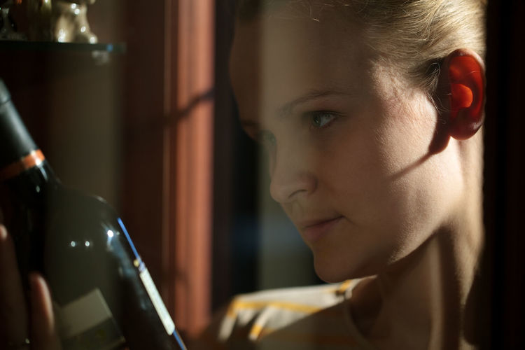 Close-up of young woman looking at wine bottle seen through glass