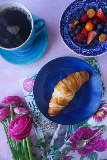 directly above of breakfast with croissant, coffee and fruit salad Croissant Breakfast Springtime Spring Flowers Ranunculus Pink Color Pink Flower Blue Blue Color Fruit Berry Fruit Berry Berries Fruit Salad Magazine Directly Above High Angle View Breakfast Time Directly Above High Angle View Plate Close-up Food And Drink Black Coffee Coffee Beverage Coffee Cup Hot Drink Coffee - Drink