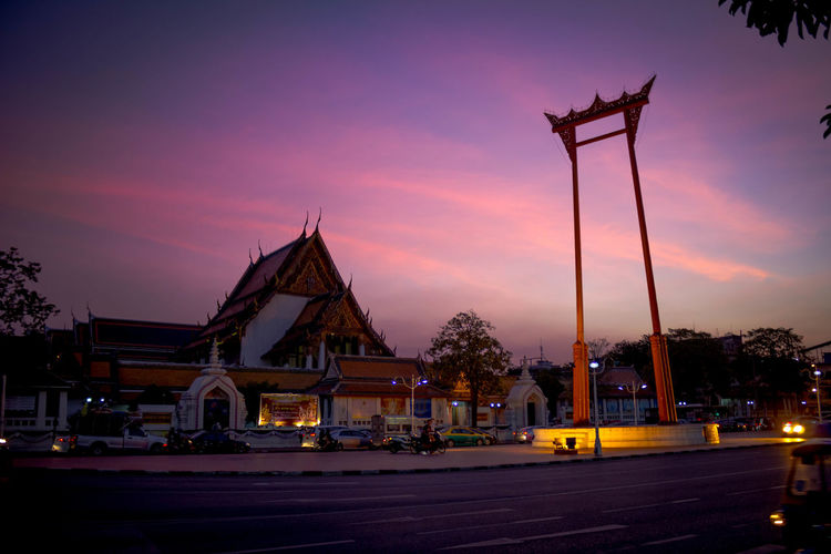 When safety changes history: This is the Giant Swing at Wat Suthat standing at 21.15 meters tall. For a long while it was the spot of an annual swinging ceremony known as Triyampavai-Tripavai where Thai men swing from the top trying to grab a suspended bag of coins with their teeth that unfortunately not everyone finished successfully (and not being successful in this case often meant death). In 1935 this risky ritual was cancelled because of the number of accidents. Safety first, my friends! Bangkok City Hall Gate Giant Swing Red Sightseeing Thailand Wat Suthat Worship Architecture Bamboo Building Exterior Built Structure City History Illuminated Night No People Outdoors Sky Street Sunset Swing