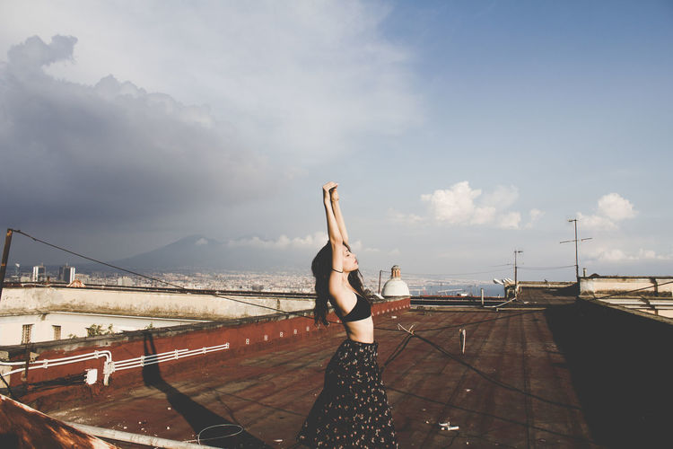 Woman Exercising On Roof Against Sky