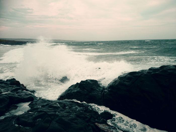 Wave splashing on rock at shore against sky