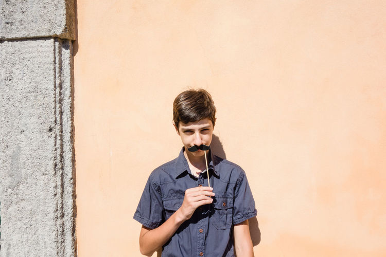 Teenagers posing with party props making funny faces under the sun against a wall Beard Boy Day Moustache Movember One Person Outdoors Paper Standing Young Adult