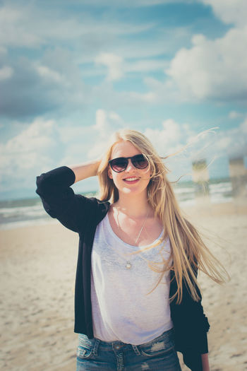 Baltic Sea Latvia Liepaja Beach Beautiful Woman Blond Hair Casual Clothing Clouds Fashion Front View Girl Glasses Hair Lifestyles Long Hair One Person Outdoors Real People Sea Smiling Standing Summer Sunglasses Young Adult Young Women