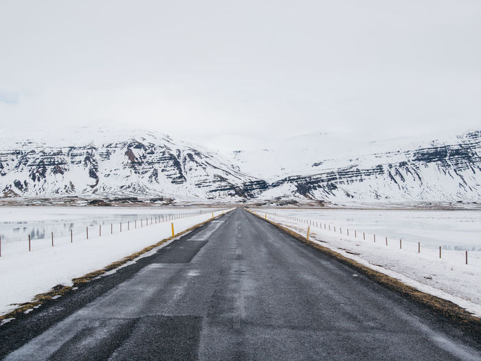 Empty Road Amidst Landscape Against Sky During Snowfall