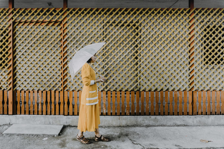 Story of a broken umbrella Protection Day One Person Outdoors People Adult Adults Only One Woman Only Yellow Umbrella White Orange Color Background EyeEmNewHere Walking Alone EyeEm Ready   The Portraitist - 2018 EyeEm Awards The Fashion Photographer - 2018 EyeEm Awards A New Beginning International Women's Day 2019