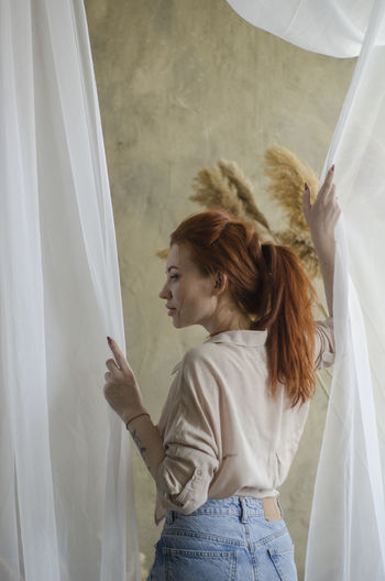 Side view of woman standing against white curtain
