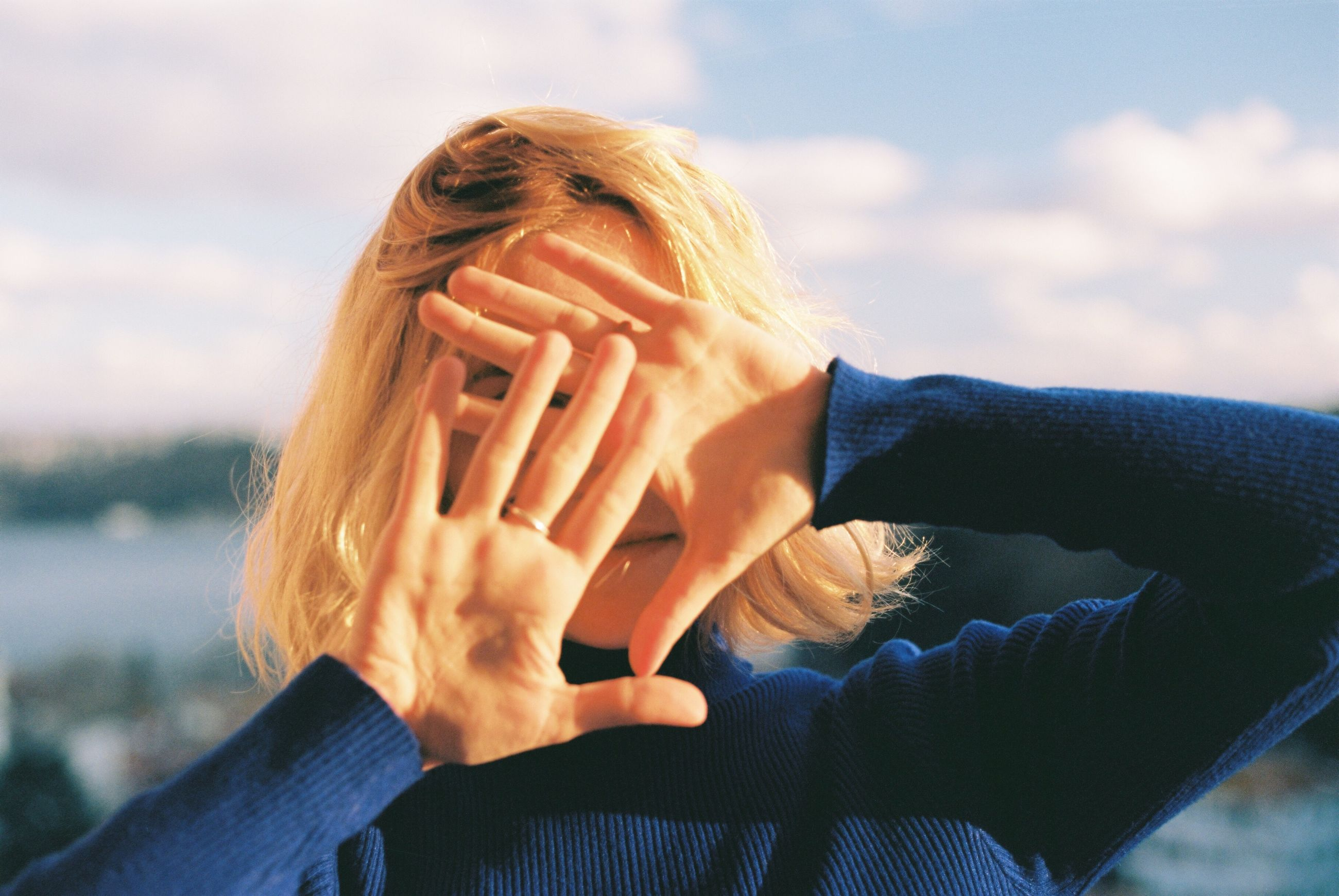 one person, headshot, leisure activity, real people, lifestyles, portrait, hand, obscured face, human hand, focus on foreground, sky, women, front view, adult, human body part, nature, unrecognizable person, covering, day, human face, outdoors, finger, warm clothing