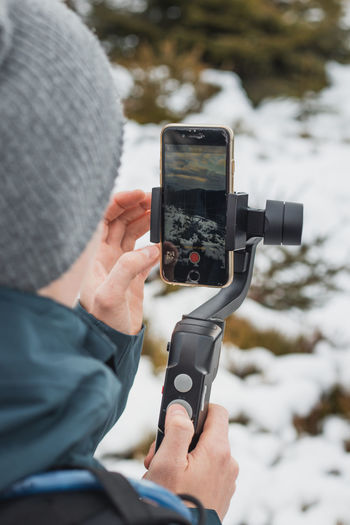 Midsection of person photographing with mobile phone in winter