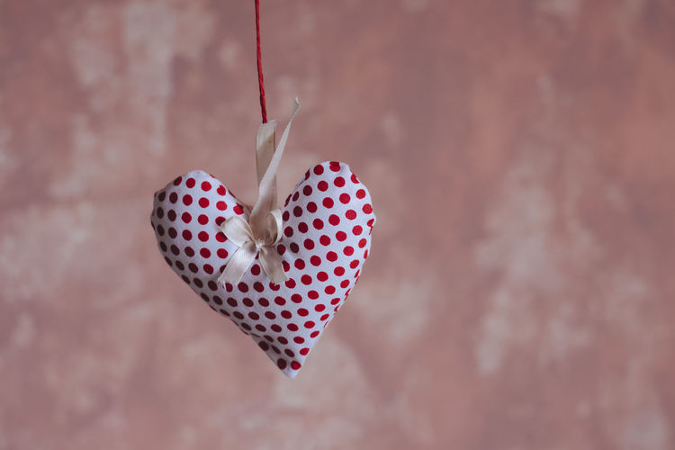 Close-Up Of Heart Shape Decoration Hanging Against Wall