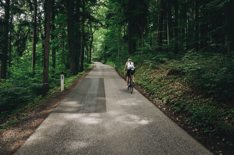 Woman riding her roadbike on road in forest in the austrian alps