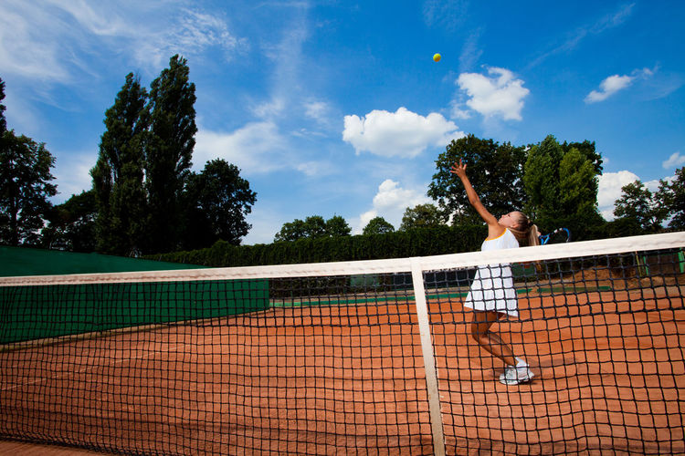 Young tennis player hitting a ball over the net on the court Playing Sport Tennis Court One Person Leisure Activity Lifestyles Cloud - Sky Sky Activity Real People Tennis Ball Young Adult Tennis Racket Racket Healthy Lifestyle Adult Taking A Shot - Sport Competition Human Arm Skill  Outdoors Hitting Arms Raised