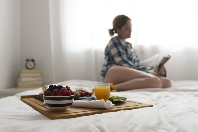 Midsection of woman sitting on table