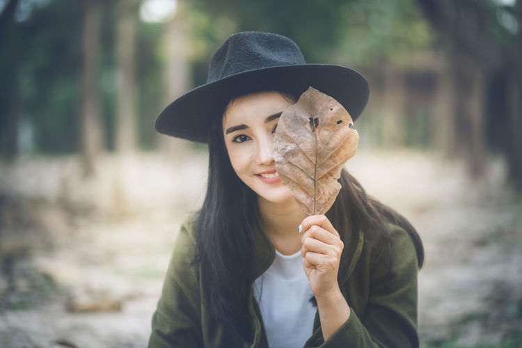 Portrait Of Young Woman Holding Dry Leaf