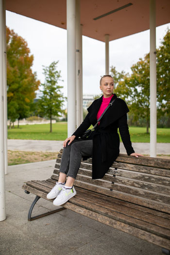 Full length of young woman sitting on bench outdoors