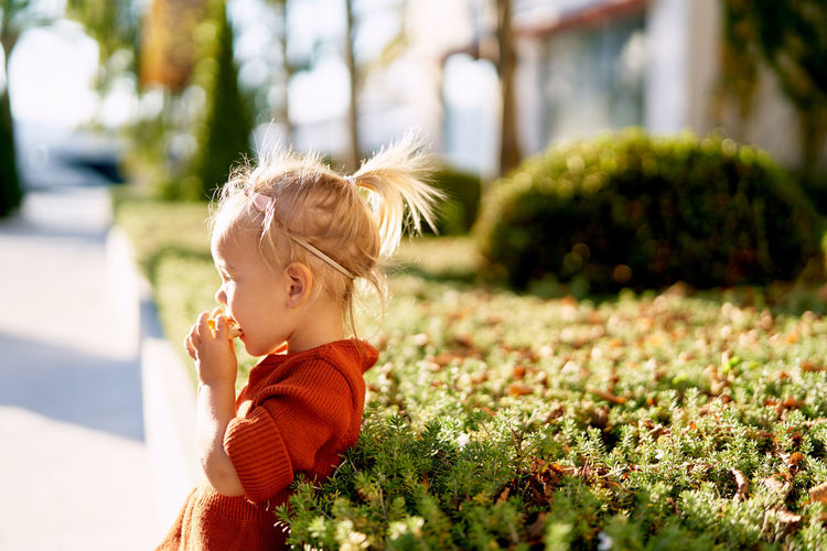 Side view of cute baby girl outdoors