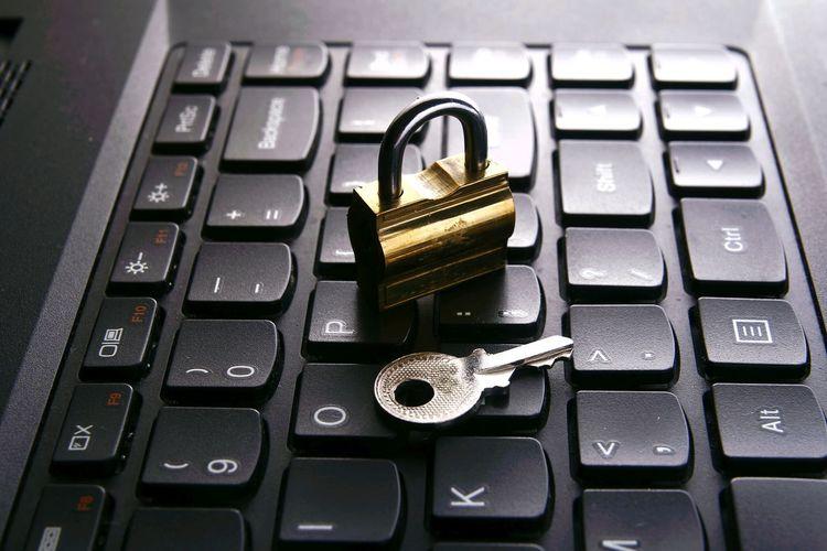 Close-up padlock and key on of computer keyboard
