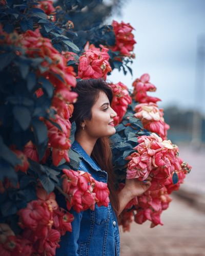 Low angle view of woman standing by red flowering plant