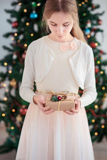 Portrait of teenage girl standing against tree