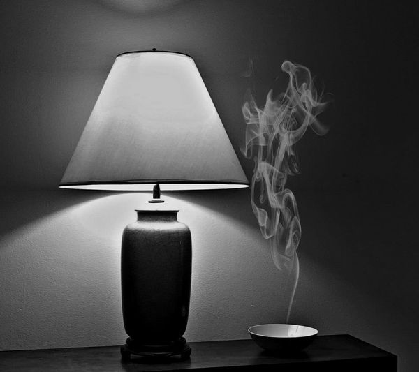 Smoke from bowl by illuminated lamp shade on table against wall at home