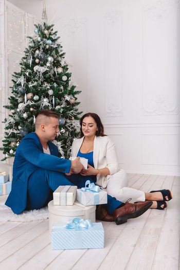 Couple sitting with gifts against christmas tree at home