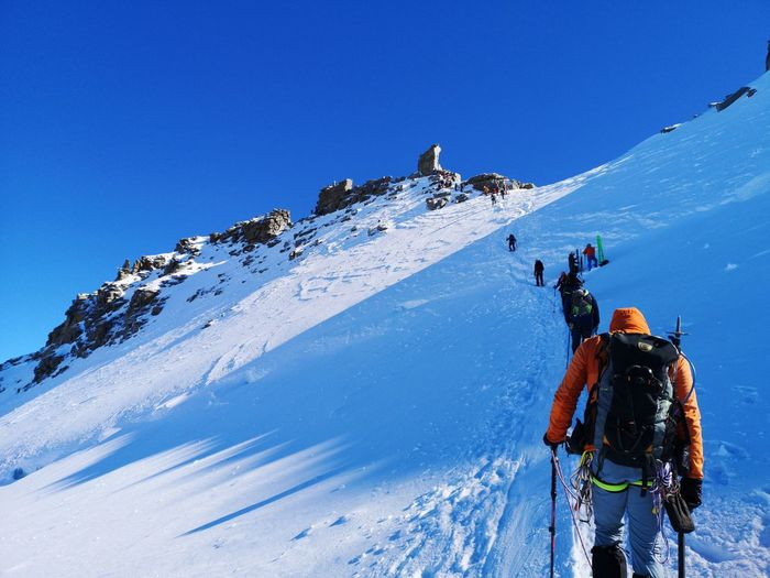 People on snowcapped mountain against clear sky during winter