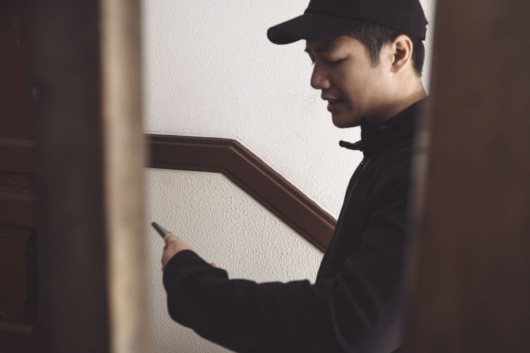 Portrait of young man standing against wall at home