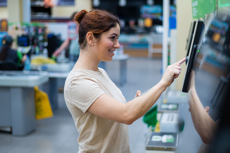Side view of smiling young woman using atm machine