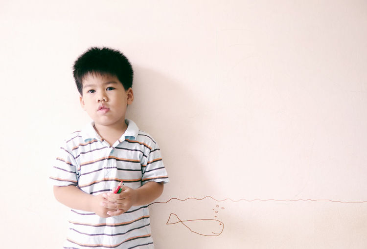 Portrait Of Cute Boy Standing By Fish Drawing On Wall