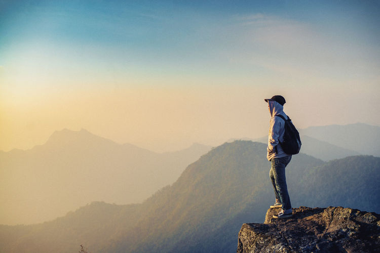 Side view of man standing on rock against sky