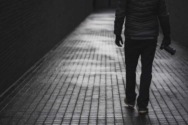 Low section of man walking on footpath with camera