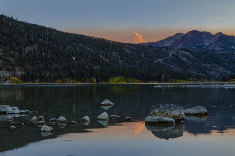 Scenic view of lake against mountains during sunset