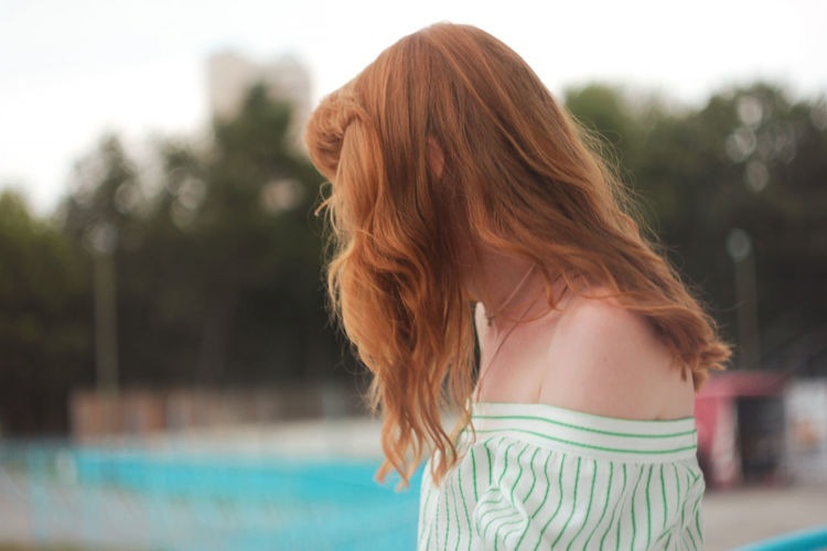 Rear view of woman standing at swimming pool