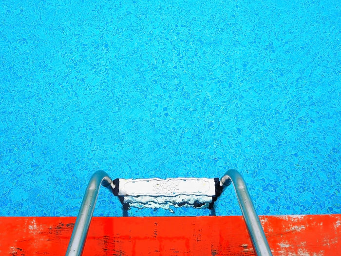 High Angle View Of Stainless Steel Ladder In Swimming Pool