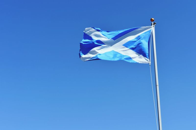 Low angle view of scottish flag waving against clear blue sky during sunny day