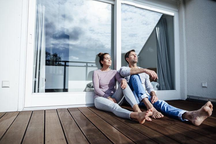 People sitting on hardwood floor at home