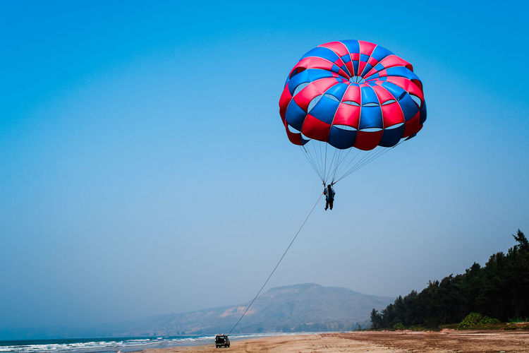 People parasailing over sea against clear blue sky