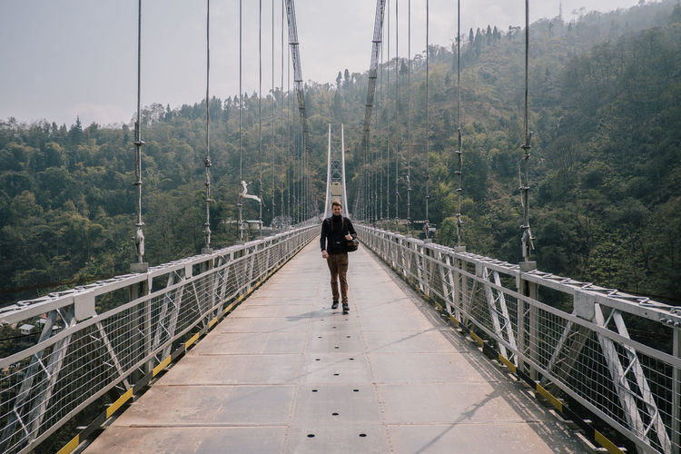 Man walking on footbridge
