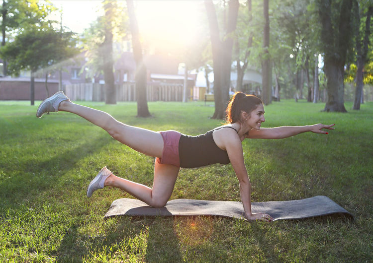 Side view of woman exercising at park