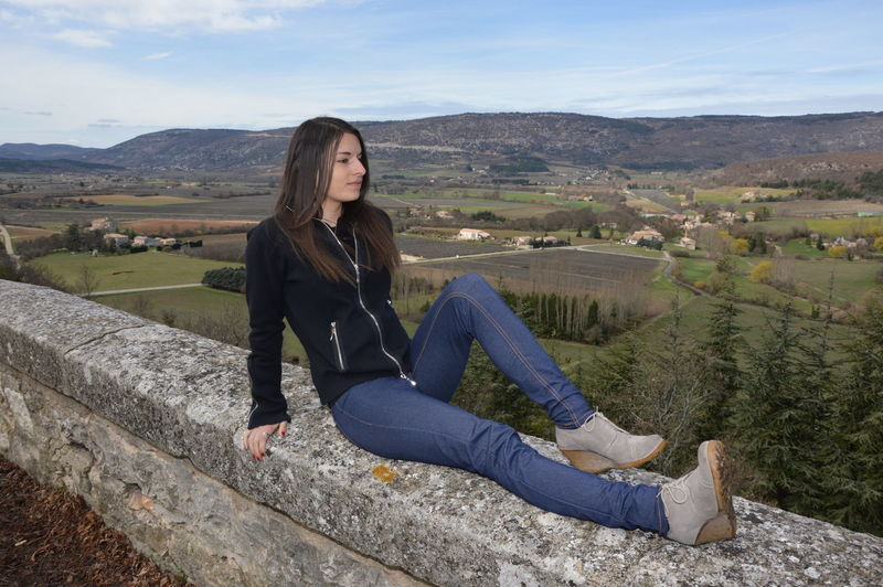 Portrait of young woman sitting on mountain against sky