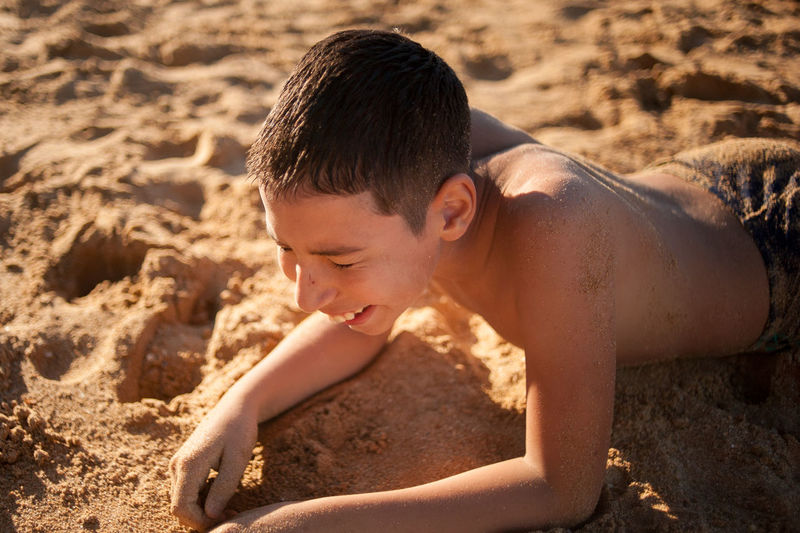 High angle view of shirtless boy on sand at beach