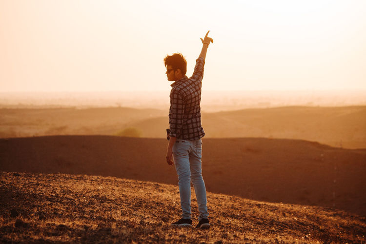 One Person Land Full Length Standing Sky Real People Casual Clothing Leisure Activity Human Arm Lifestyles Nature Field Arms Raised Environment Sunset Beauty In Nature Non-urban Scene Scenics - Nature Tranquility Outdoors