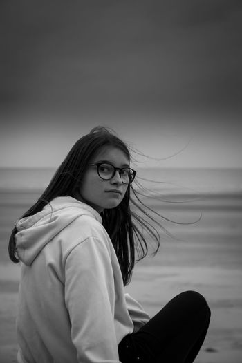 Portrait of girl sitting at beach against sky