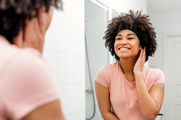 Bathroom Indoors  Young Women Lifestyles Standing Curly Hair Domestic Bathroom Mirror Portrait Hairstyle Beautiful Woman Looking Mirror Morning Routine African American Real People Bath Mixed Race Skin Care Selective Focus Healthy