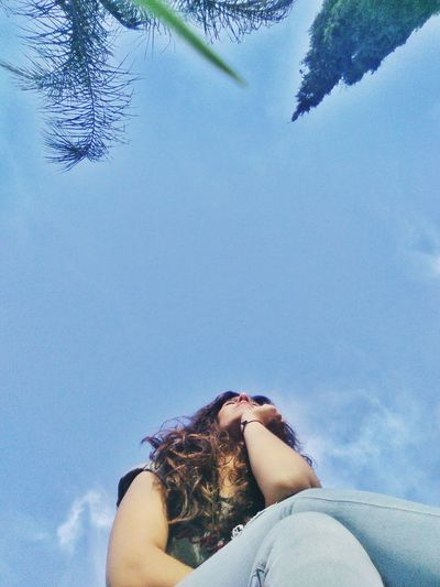 Low angle view of woman relaxing against sky