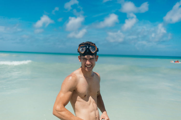 A young man wearing snorkeling goggles standing infront of the Atlantic ocean looking at the camera and being goofy Atlantic Ocean Elated Enthusiasm Happy Happy People Ocean View Real People Scuba Diving Snorkeling Snorkeling Mask Snorkelingspot Snorkelling Vacation Destination
